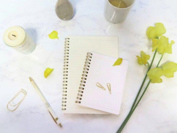 テーブルの上のメモ帳と花